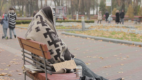 Hungry beggar sitting alone in cold park, many people passing by indifferently Live Action
