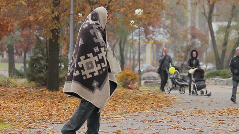 Unhappy beggar limping in autumn park, social vulnerability and poverty problem Live Action