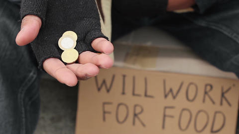 Poor man begging for change, holding coins in his hands, will work for food sign Footage
