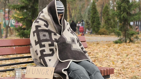 Hungry homeless frozen man sitting on bench and trying to get warm, poverty Footage