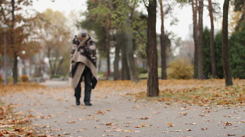 Mentally ill male wrapped in blanket walking in park, health problems, homeless Live Action