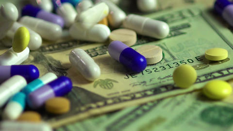 Pills falling on dollar banknotes, expensive medication, pharmaceutical business Footage