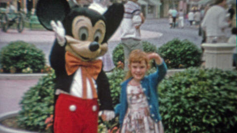1962: Mickey mouse waving with redhead little girl at Disneyland Footage