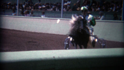 1969: Horse harness racing drivers going around the race track Footage