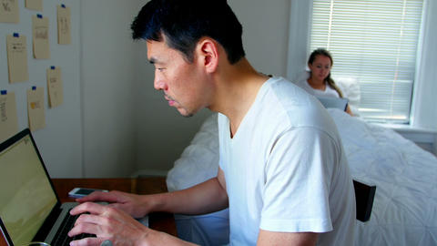Man using laptop while woman using digital tablet Footage