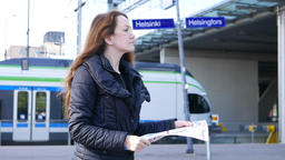 Tourist girl get lost on railway station, hold city map and look around Footage