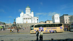 Slide shot of Senate Square and Helsinki Cathedral, sunny day, touristic buses Footage