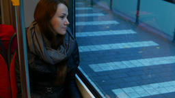 Woman ride in tram at evening, positive emotion on her face, look out window Footage