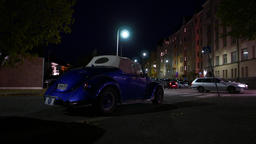 Old open-top car with soft roof parked at night street, rear side view Footage