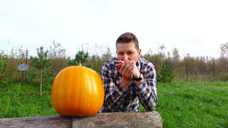 Young farmer celebrate good crop, stand by large pumpkin and play on harmonica Footage