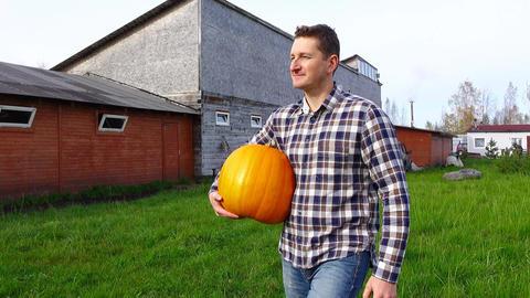 Local man carry large orange pumpkin, walk at farm backyard, POV orbiting shot Footage