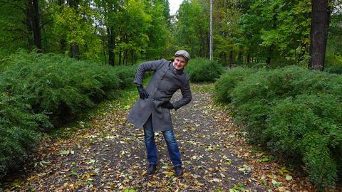 Funny man do jocose exercises at autumn park path, slow motion shot Footage