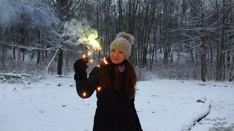 Happy girl hold in hand brightly shining sparkler, snowy park opening, slowmo Footage