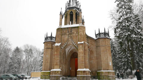 Romantic orthodox church of apostles Peter and Paul in snowy park, tilt down Footage