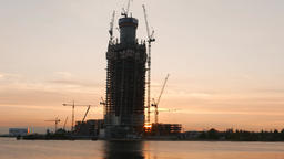Tall tower frame against sunset sky, standalone skyscraper development site Footage