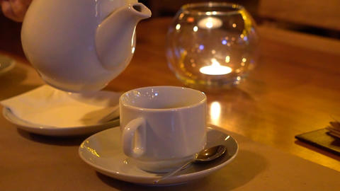 Slow Motion: Hot Tea Flowing To A Tea Cup From A Teapot - Close Up Slow Motion Live Action