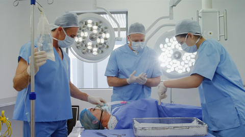 Surgery team discussing while operating a patient in an operating room Live Action