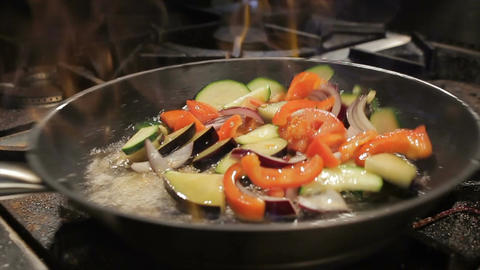 Person Shakes Pan with Frying Vegetables above Open Flame Footage