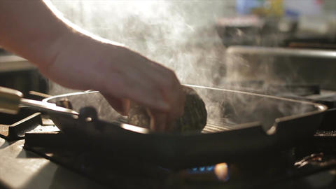 Closeup Hand Turns Meat Lump to Other Side on Pan Footage