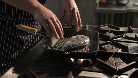 Closeup Hands Put Fish into Pan on Stove Footage