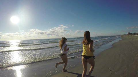 Girlfriends jogging along the beach Live Action