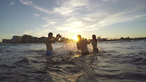 Group of friends teasing one another and playing with water in the sea Live Action