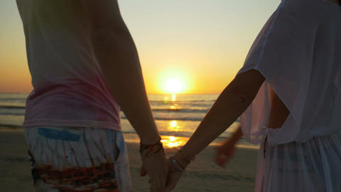 Romantic couple holding hands and walking on the beach towards the sea Footage