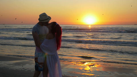 Couple of young man and woman meeting on a sandy beach and kissing with passion  Footage