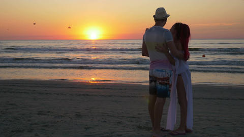 Couple hugging and kissing on the shore of a sandy beach at sunset Footage