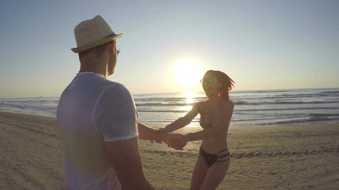 Young couple holding hands and running on beach towards the sea Footage