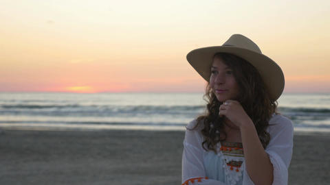 Woman with hat posing on the beach at sunrise Footage
