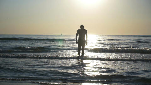Silhouette of a young man going into the sea in slow motion Footage