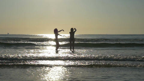 Silhouettes of two beautiful girl friends having fun and playing in the ocean in Footage
