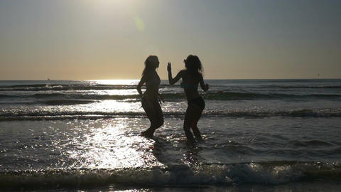 Women dancing in the water on the shore of a beach in slow motion Live Action