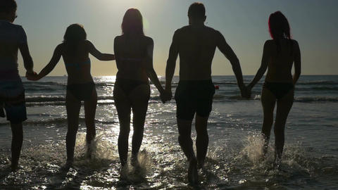 Group of friends holding hands and walking towards the sea at twilight in slow m Footage