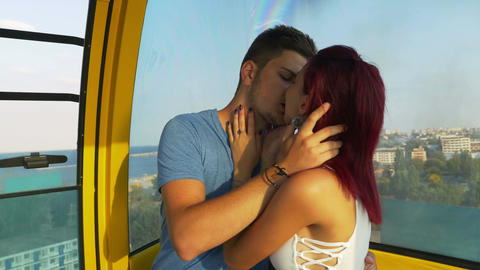 Lovers kissing passionately in ropeway at the seaside Footage