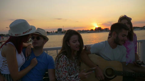 Boys and girls sitting on a bench and singing on a pontoon Footage