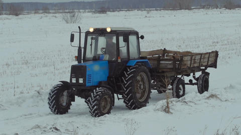 Blue tractor with trailer rides on snow field Footage