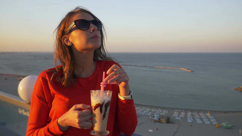 Young teenager woman drinking a frappe on a terrace with a sea view Footage