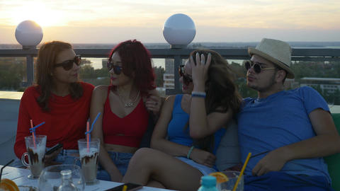 Group of friends on a rooftop bar having a chat and enjoying a drink Footage