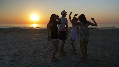 Male dancing with three female friends on the beach at sunset Footage