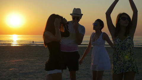 Young man dancing with three female friends on the shore of the ocean at twiligh Footage