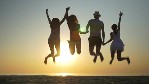 Four friends jumping on a beach at sunset in slow motion Footage