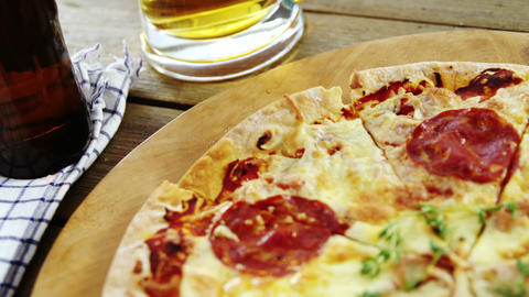 Delicious pizza with a glass of beer and beer bottle Live Action