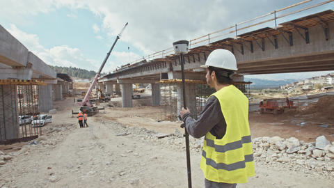 Construction engineer using a GPS device at a construction site Live Action