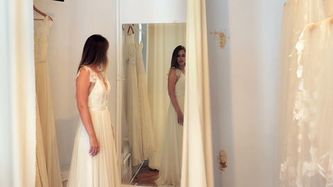 Beautiful woman trying on wedding dress in a shop Footage