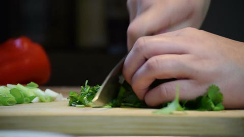 Close-up of chefs hands roughly chopping preparing coriander with knife for cook Footage