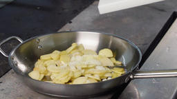Cooking stir fried potatoes in boiling oil on pan slow motion HD video close up  Image