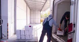 Delivery worker loading cargo van cardboard boxes in storage warehouse 4k video Footage