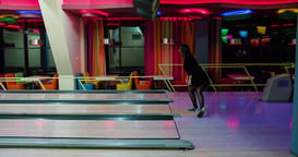 Woman playing bowling throwing ball lane 4k leisure video. Girl rolling ball Footage